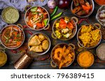 Small photo of Assorted indian food set on wooden background. Dishes and appetisers of indeed cuisine, rice, lentils, paneer, samosa, spices, masala. Bowls and plates with indian food