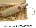 Small photo of A bottle of exclusive wine wrapped in the paper and sealed with the blank wax seal in the wooden box with the blades of hay isolated on the white background. Available space for a logo or text