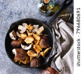 Small photo of Heap of fresh forest porcini boletus and chanterelles mushrooms in iron cast pan with olive oil and salt, served won textile napkin, knife over gray texture background. Top view, space. Square image