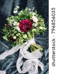 Small photo of Bouquet of marsala and white flowers with greenery decorated by ribbons, laying on grey velour cloth