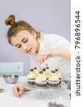 young woman decorates cupcakes | Shutterstock . vector #796896544
