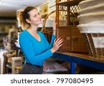 Small photo of Teenager female choosing wicker ambry in decoration and furniture store