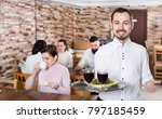 cheerful male waiter serving a... | Shutterstock . vector #797185459