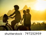 Small photo of RIO DE JANEIRO - MARCH 20, 2017: Visitors pass along Ipanema Beach to Arpoador, a popular spot to take in the sunset against the silhouette backdrop of Two Brothers Mountain.