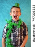 Small photo of A young boy dressed in St. Patrick's day garb yelling with his eyes closed.