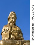 Small photo of Big Golden Guanyin holding vase in Chinese Temple, brass statue of goddess mercy in joss house