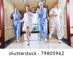Doctor and nurse running in hallway of hospital - stock photo