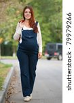 Full length of 9 months pregnant woman walking on street - stock photo