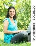 Beautiful young woman using laptop outdoors. - stock photo