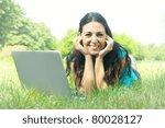 Smiling girl using laptop outdoors. - stock photo