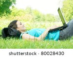 Student using laptop outdoors. - stock photo