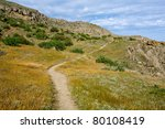 pathway in mountains among dry grass - stock photo