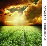 green field with road under dramatic sky - stock photo