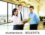 An attractive asian female leader presents a document to her male coworkers in an office setting - stock photo