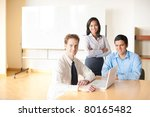 A caucasian businessman leads a team meeting with his hispanic and asian coworkers using a laptop - stock photo