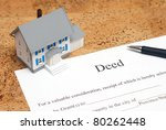 A scale house on some forms for a deed to conceptualize on the financial investment. - stock photo