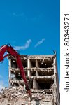 Red digger demolishing a four story building - stock photo
