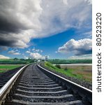 railroad to horizon under cloudy sky - stock photo