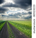 dirty road to cloudy horizon - stock photo