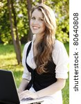 Young pretty woman with laptop sitting on the bench in a park. - stock photo
