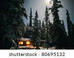 Small photo of Yukon/Alaska trapline log-cabin fully illuminated at full-moon night in snowy winter.