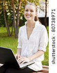Laughing pretty woman with laptop sitting on the bench - stock photo
