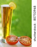 cold beer, tomato and lemon. - stock photo