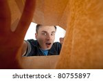 frightened young man looking to paper bag - stock photo