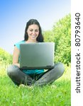 Beautiful happy young woman using laptop outdoors. - stock photo