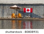 Two wooden chairs and Canadian Flag - stock photo