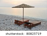 two chairs and umbrella on the beach - stock photo
