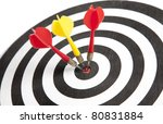 Three Darts hitting the middle of dartboard - stock photo