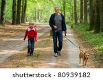 Stock photo grandpa and grandchild are walking the dog in the forest 80939182