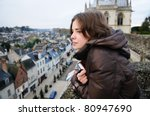 Portrait of young woman looking on small town (France, Amboise) - stock photo