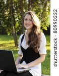 Young pretty woman with laptop sitting on the bench in a park - stock photo