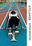 Man in a start block on an athletic track - stock photo