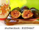 fig fruits and spoon of  honey on green background - stock photo