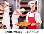 A male baker holding freshly baked croissants in bakery - stock photo