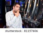 Man Sitting By The Slot Machin...