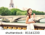 Paris woman smiling eating the french pastry macaron in Paris. Eiffel tower and Pont Des Invalides in the background. Cute beautiful mixed race Asian Caucasian female model. - stock photo