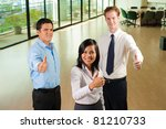 Happy team of three diverse business people, Asian, Hispanic and Caucasian, standing, displaying thumbs up for approval while looking at camera seen down from high angle in large office. Horizontal - stock photo