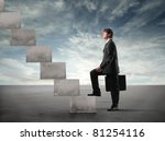 Businessman stepping up a staircase - stock photo