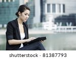 Asian Business woman using touch screen tablet in City - stock photo