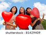 Three Young Women Holding Red...