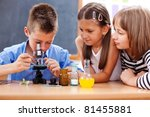 Small photo of Eminent elementary school boy looking into microscope while girls are watching