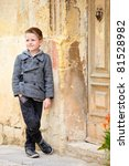 Portrait of six years old boy outdoors in city - stock photo