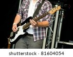 musician playing a bass guitar on stage - stock photo