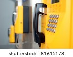 yellow public telephones with emergency icons - stock photo