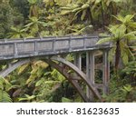 A concrete bridge in the middle of the jungle surrounded by palm trees - stock photo