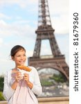 Paris woman and Eiffel Tower. Girl eating french crepe / pancake in front of Eiffel Tower, Paris, France. Mixed race Chinese Asian / Caucasian tourist. - stock photo